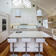 ​​​​​​​Existing rich Matai flooring is contrasted with cool cabinetry, benchtop, interior design, kitchen, Damien Hannah, Timber Floor, Matai, white