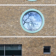 The green glazed brick and circular windows of architecture, blue, daylighting, daytime, facade, sky, wall, window, white, brown