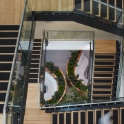 A central stairwell provides views right through the architecture, balcony, building, facade, glass, handrail, home, house, residential area, stairs, window, black