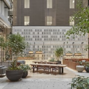 A patterned wall hides lift entries from atrium apartment, condominium, courtyard, facade, mixed use, neighbourhood, outdoor structure, patio, plaza, real estate, residential area, urban design, gray, brown
