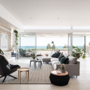 Exterior rock walls are continued as interior accents timber floor, furniture, apartment, interior design, living room, table, white, furniture,  furnishings, Banham Architects, Contemporary