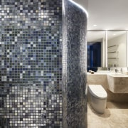 ​​​​​​​This bathroom features a blue-metallic mosaic wall and architecture, bathroom, ceramics, floor, flooring, apartment, interior design, mosaic, tile, wall, gray, Archer Design