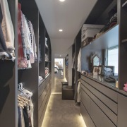 Dark-toned and admitting natural light through a louvred architecture, walkin wardrobe, concealed lighting, McMahon & Nerlich
