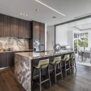 While the LED strip ceiling lighting is understated architecture, cabinetry, countertop, benthtop, design, dining room, floor, flooring, furniture, hardwood, home, house, interior design, kitchen, dining table, wood flooring, marble, Studio Italia