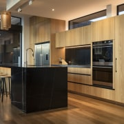 Recessed track spots above this benchtop provide a architecture, kitchen, cabinetry, countertop, cupboard, timber flooring, home, house, interior design, kitchen, wood flooring, wood stain, brown, black, lighting, feature lighting, fisher & Paykel, Eliska Lewis Architects