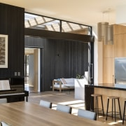 The play of wood and black is seen architecture, building, ceiling, design, dining room, floor, flooring, furniture, hardwood, home, house, interior design, living room, loft, plywood, property, real estate, room, table, wall, wood, wood flooring, black