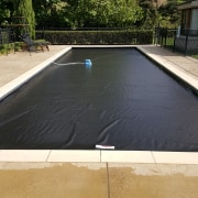 This Coverstar Eclipse Auto Pool Covers is just asphalt, composite material, concrete, daylighting, floor, grass, property, roof, swimming pool, orange