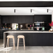​​​​​​​This living zone's dark tones balance the natural architecture, black, black-and-white, building, cabinetry, ceiling, countertop, dining room, floor, flooring, furniture, home, house, interior design, kitchen, material property, property, room, table, tile, black, white