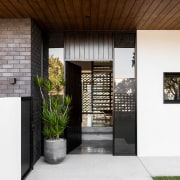 ​​​​​​​On entry to this home, guests look through architecture, building, ceiling, courtyard, door, facade, floor, flooring, grass, home, house, interior design, plant, property, real estate, residential area, roof, room, tile, white