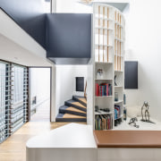 ​​​​​​​The spiral staircase in this family home by architecture, bookcase, building, ceiling, design, floor, flooring, furniture, home, house, interior design, living room, loft, material property, property, room, shelf, shelving, space, stairs, table, wall, white, white