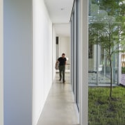 A hallway connects the main living areas with architecture, building, daylighting, door, facade, floor, glass, house, interior design, room, window, gray
