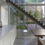 A concrete staircase appears to float within a architecture, building, ceiling, daylighting, design, floor, flooring, furniture, glass, handrail, home, house, interior design, loft, material property, metal, office, property, real estate, room, stairs, table, tile, wall, window, gray