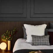 ​​​​​​​Catering to the owners' desire for a pampered bed, bed frame, bed sheet, bedding, bedroom, black, brown, comfort, cushion, design, duvet cover, floor, furniture, hardwood, home, house, interior design, lighting, nightstand, pillow, room, textile, wall, wood, black