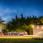​​​​​​​This home by designers Marcus Freeman and Hayden architecture, building, cloud, estate, facade, grass, home, house, land lot, landscape, landscape lighting, landscaping, light, lighting, night, property, real estate, residential area, sky, tree, yard, brown