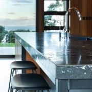 ​​​​​​​The leathered granite island benchtop adds textural interest architecture, building, cabinetry, countertop, floor, flooring, furniture, glass, granite, home, house, interior design, kitchen, marble, material property, property, room, table, tile, window, white, black