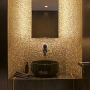 This luxurious powder room forms part of a brown, orange