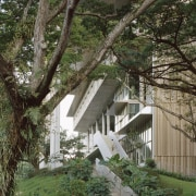 The innovative SDE4 building looks out through mature architecture, botany, branch, building, cottage, home, house, plant, property, real estate, residential area, roof, tree, yard, brown