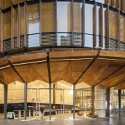 Broad folded timber awnings shade the street at architecture, building, ceiling, daylighting, lobby, brown