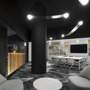 A meeting and library space overlooks the triple-height architecture, building, ceiling, design, furniture, house, interior design, lighting, lobby, night, room, table, black, gray