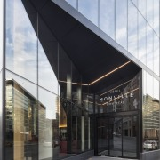 The Hotel Monville's entry continues into a low architecture, building, commercial building, corporate headquarters, facade, glass, headquarters, house, interior design, material property, mixed-use, real estate, shade, gray, black