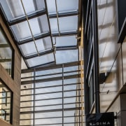 The central atrium runs right through the building architecture, building, ceiling, commercial building, daylighting, facade, glass, house, metal, real estate, roof, window, gray, black