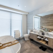 Sudima Christchurch City features natural materials throughout, including architecture, bathroom, building, ceiling, floor, furniture, home, house, interior design, property, real estate, room, suite, tile, white, gray