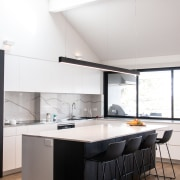 ​​​​​​​The island's cantilevered benchtop allows for casual breakfast white