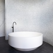 A black floor-mounted tub pourer connects with the white, gray