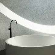 Curved tub, curved mosaic wall and curved light gray, white
