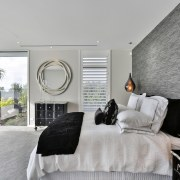 Eclectic furniture, mirror and pendant choices provide interest