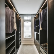 This walk-in wardrobe features built-in joinery in smoked