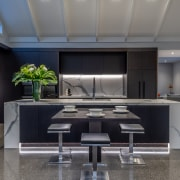 This two-tone kitchen's pre-dominant dark cabinetry and marble-look