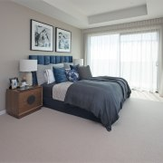 Diaphanous curtaining, a padded headboard and comfort-under-foot carpet