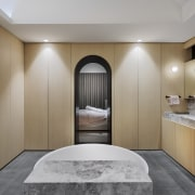 ​​​​​​​Warm wood laminate surfaces conceal wardrobe facilities in