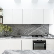​​​​​​​This white kitchen's feature benchtops and splashback are