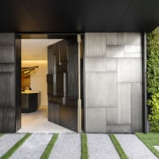 ​​​​​​​A custom designed pivoting front door sits beside