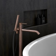​​​​​​​This copper-finish tub pourer adds luxe without bling