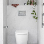 The toilet has its own private niche. -