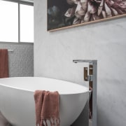 The sculptural tub is matched by a floor-standing