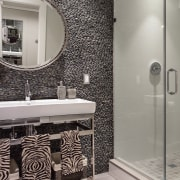 This powder room has a feature stone wall.