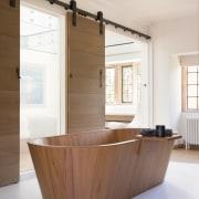 The bespoke sculptural teak bath has a remote-operated