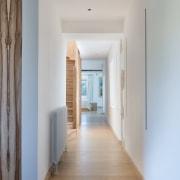 Pale oak flooring running the hallway's length.