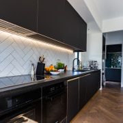 An iridescent wall tile features in the kitchen's