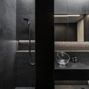The expanse of dark grey wall tiles that architecture, bathroom, black, black-and-white, building, floor, flooring, house, interior design, material property, monochrome photography, photography, plumbing fixture, property, room, tap, tile, black