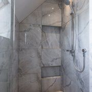 The generous shower zone is set at the architecture, bathroom, cement, floor, interior design, plumbing fixture, property, room, shower, tile, wall, gray