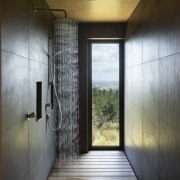 Cocooned in moody, large-scale tiles the shower space