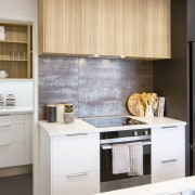 The kitchen's attractive grained wood and white cabinetry
