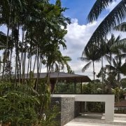 The cladding is a mix of textural surfaces, architecture, arecales, botany, building, eco hotel, estate, home, house, landscape, palm tree, plant, property, real estate, resort, sky, tree, tropics, vacation, vegetation, black, brown