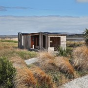 Small Project Architecture: Invercargill Estuary Walkway Shelters by cottage, ecoregion, ecosystem, grass, home, house, land lot, landscape, plant community, prairie, property, real estate, sand, shack, shrubland, sky, gray