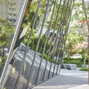 Mirror facade panels reflect greenery while above nature gray